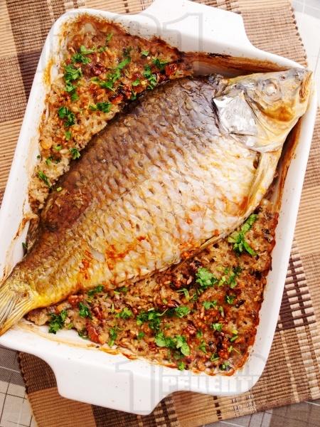 Вкусен пълнен шаран на фурна за Никулден с ориз, орехи, лук и стафиди печен под фолио - снимка на рецептата